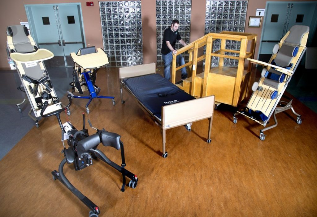 At Equipment including a gait trainer, standers, and a bed