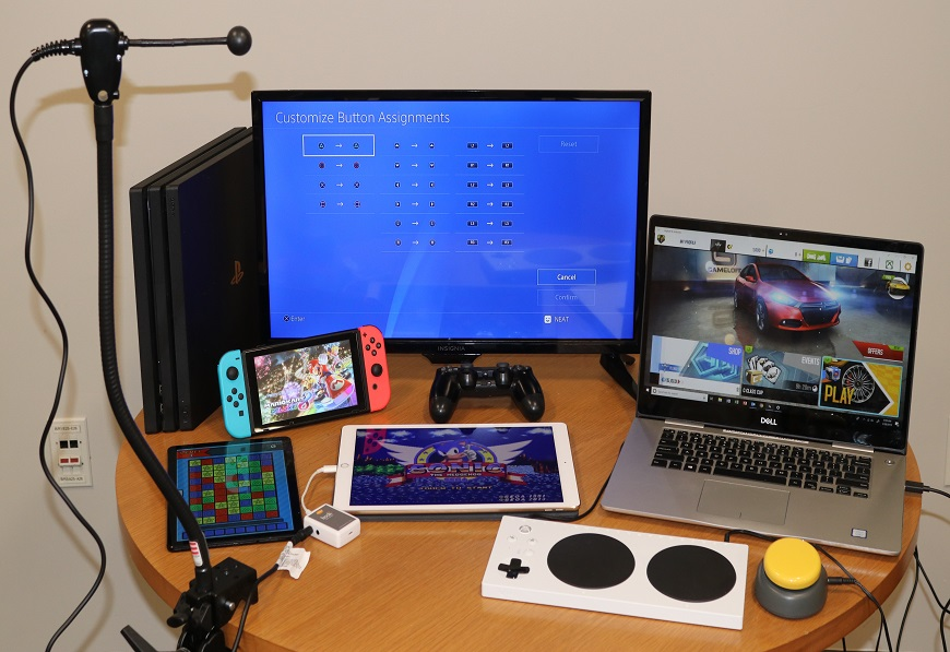 Several gaming platforms on a table representing gaming accessibility options, including a Playstation 4's button reassignment screen, an Xbox Adaptive Controller, a Nintendo Switch with Mario Kart 8, a Android Tablet running Collapsus, and an iPad Pro running Sonic the hedgehog. Switches can also be seen including an Ultimate Switch