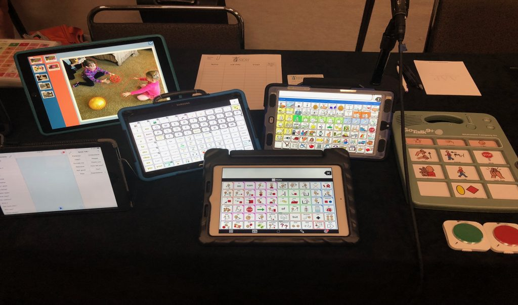 Various AAC devices displayed on a table