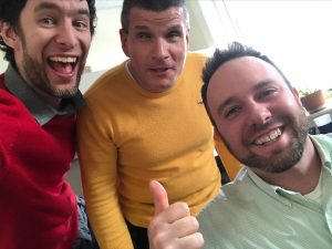 Adam wearing red, Steve wearing yellow, and Kris wearing green, all smiling. They're like a stop light!