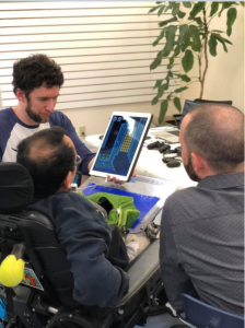 Adam helping a gamer using a wheelchair play Mario Run on the iPad using an Ultimate Switch